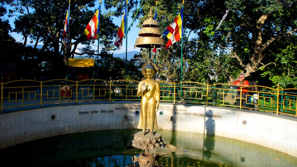 Swayambhunath which includes a pond, a statue or sculpture and religious aspects