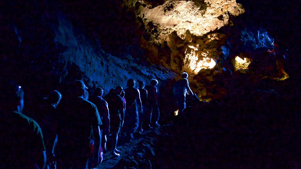 Cueva de los Verdes featuring caving and caves as well as a large group of people