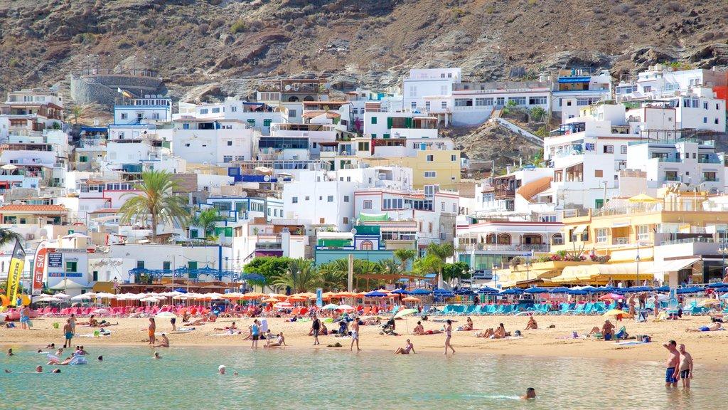 Playa de Mogan which includes a beach, a coastal town and general coastal views