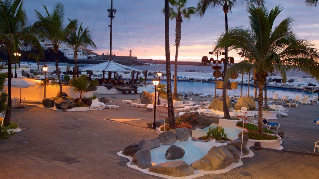 Puerto de la Cruz which includes a sunset, a luxury hotel or resort and a pool