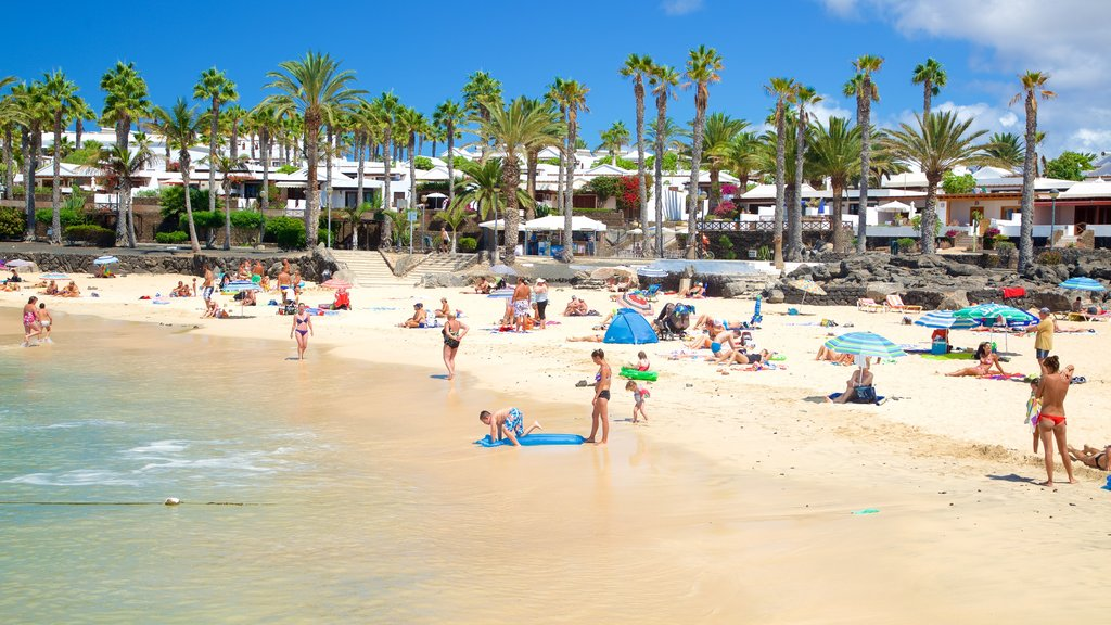 Playa Blanca featuring a beach and general coastal views as well as a large group of people