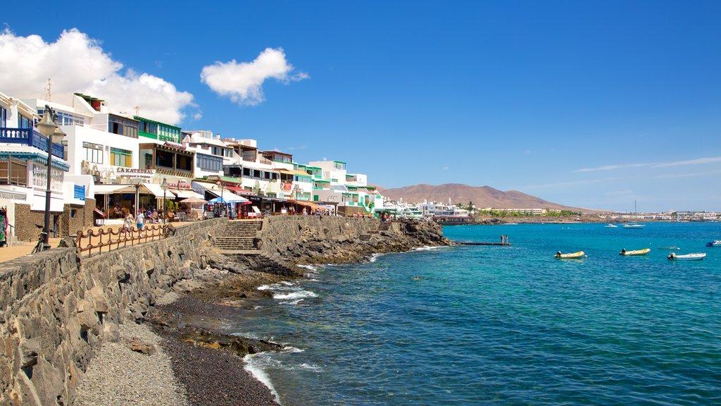Playa Blanca featuring a coastal town, rocky coastline and boating