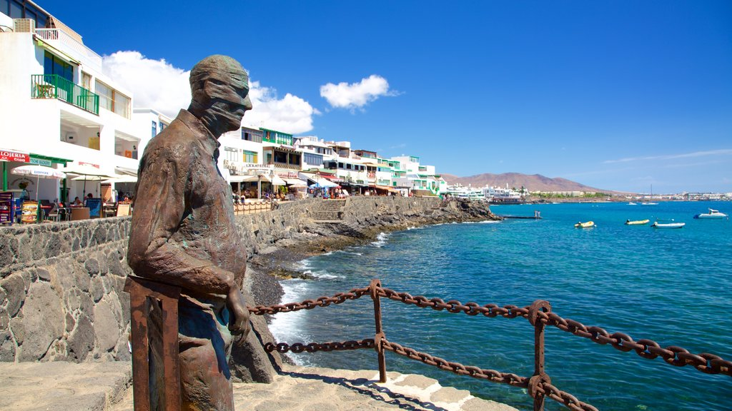 Playa Blanca which includes a statue or sculpture, a coastal town and rocky coastline