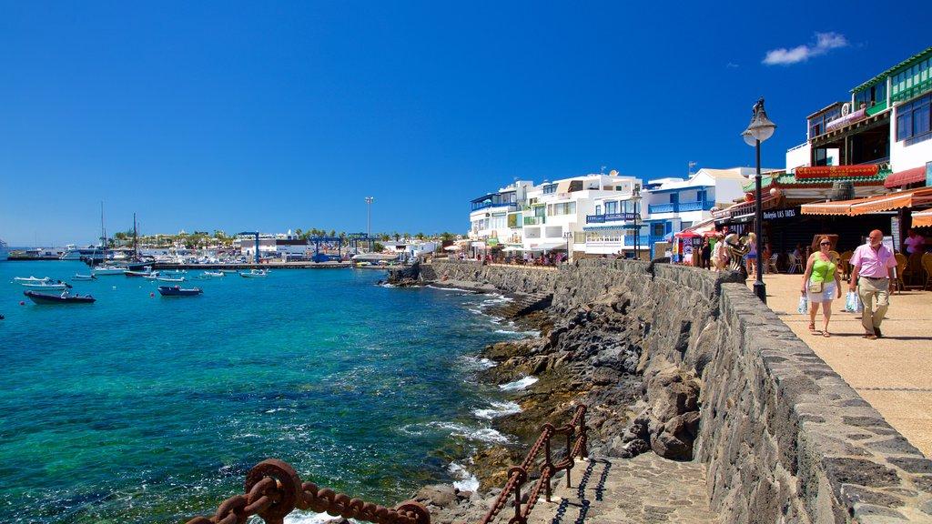 Playa Blanca showing rugged coastline, boating and a coastal town