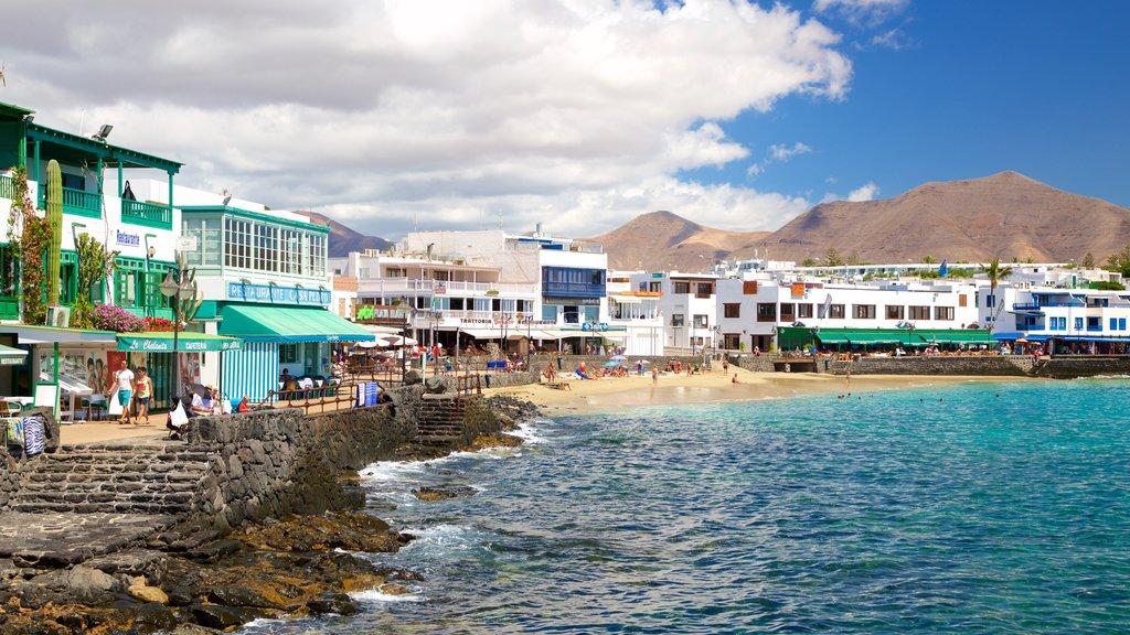 Playa Blanca featuring a beach, a coastal town and rocky coastline