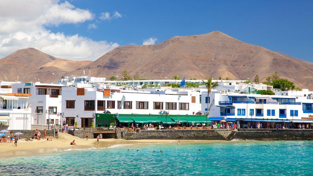 Playa Blanca showing a coastal town, a sandy beach and general coastal views