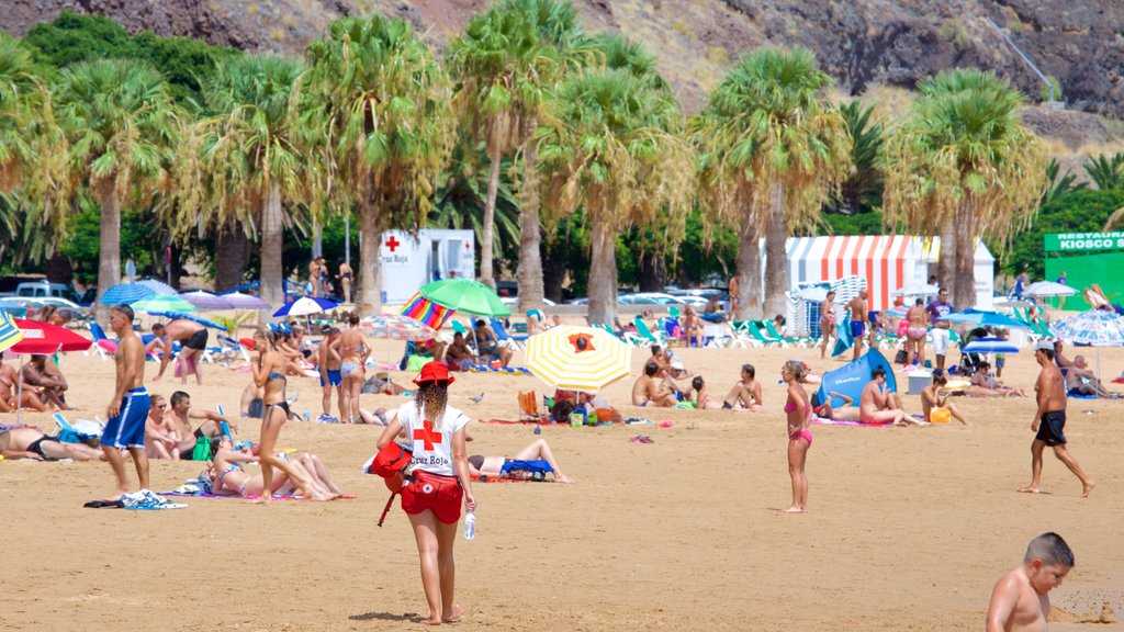 Teresitas Beach which includes general coastal views and a sandy beach as well as a large group of people