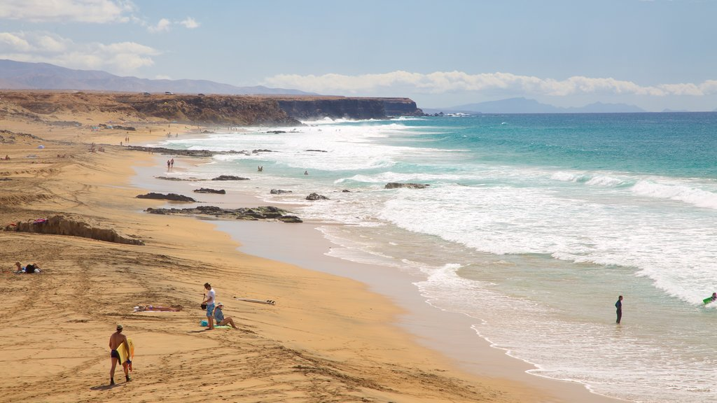Cotillo Beach which includes waves, rugged coastline and a sandy beach