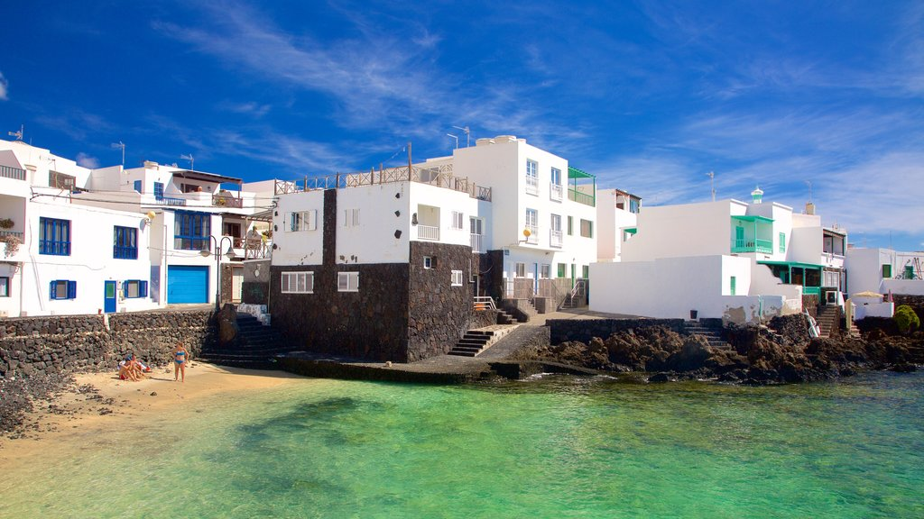 Lanzarote featuring rocky coastline, a coastal town and a beach