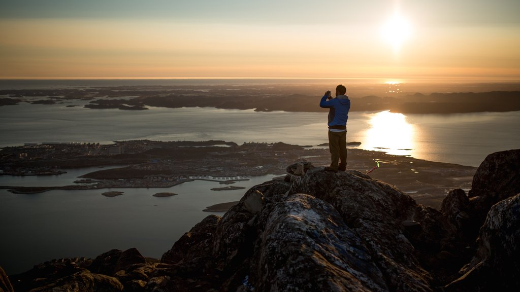 Nuuk which includes a sunset and a lake or waterhole as well as an individual male