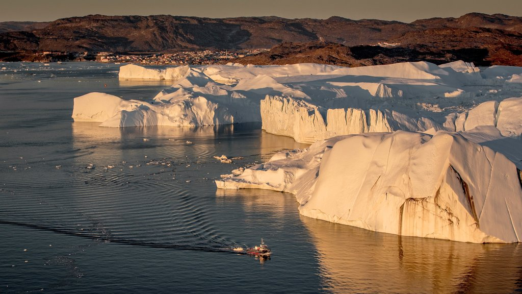 Ilulissat featuring snow, rugged coastline and boating