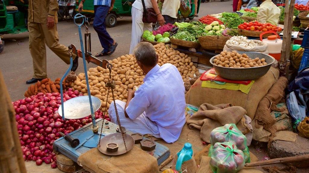 Manek Chowk que incluye mercados y comida y también un hombre