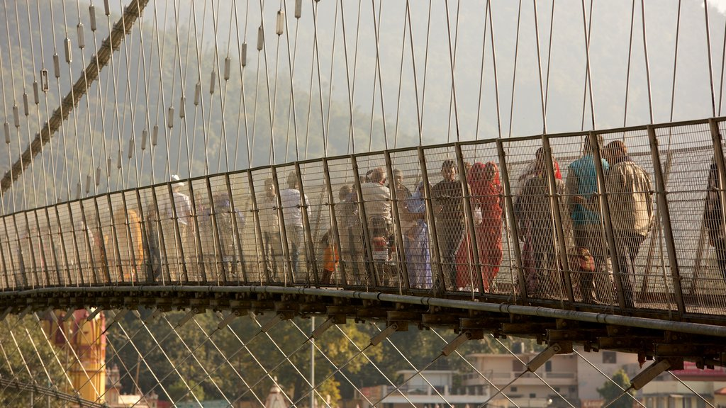 Ram Jhula featuring a suspension bridge or treetop walkway as well as a small group of people