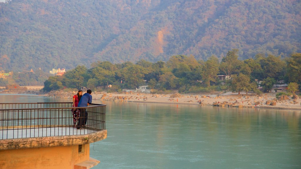 Ram Jhula which includes a river or creek and tranquil scenes as well as a small group of people