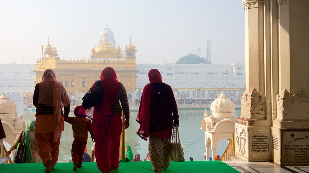 Golden Temple featuring heritage elements and a lake or waterhole as well as a small group of people