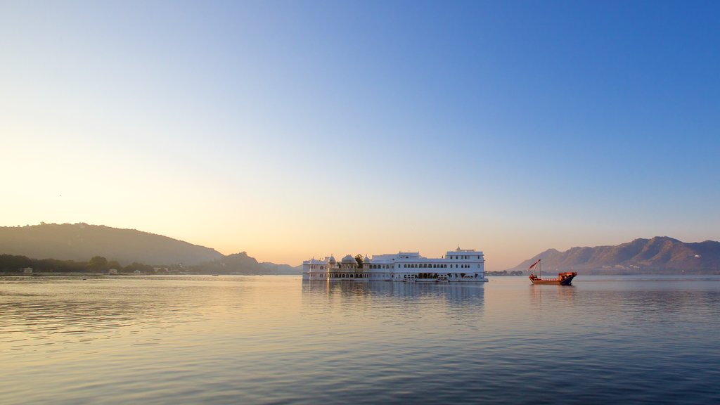 Lake Palace which includes a lake or waterhole, a sunset and island views