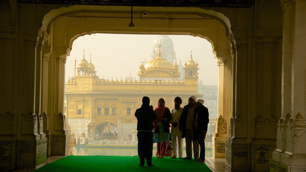 Golden Temple featuring heritage elements and a temple or place of worship as well as a small group of people