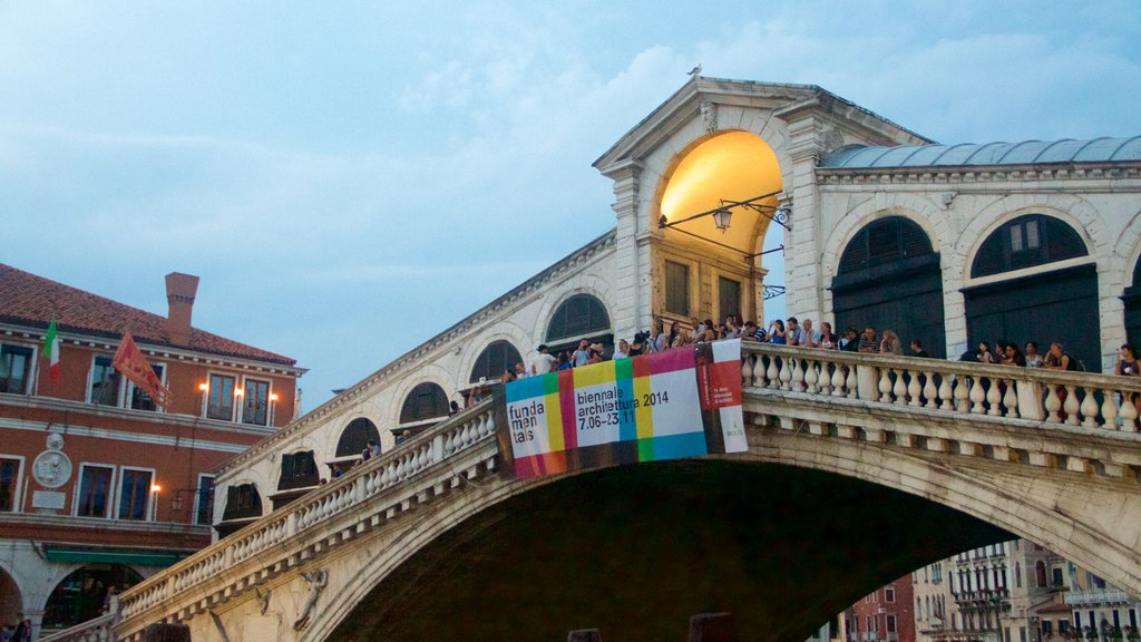 Rialto Bridge showing a bridge and signage as well as a small group of people