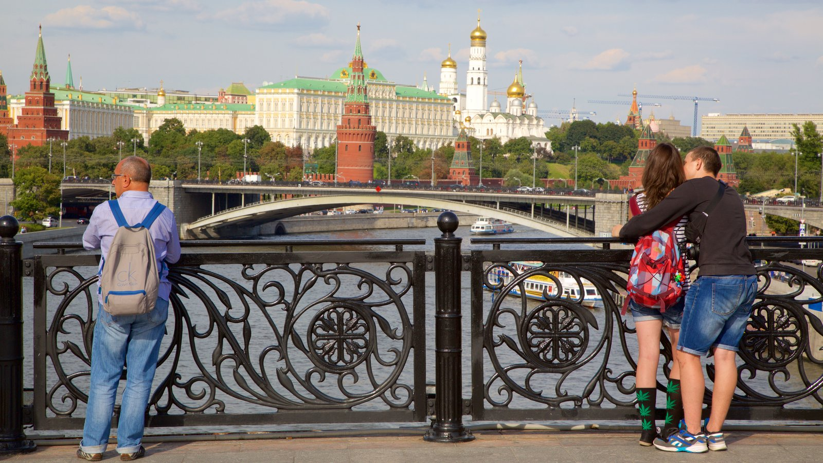 Moscow Kremlin showing a bridge and a river or creek as well as an individual male
