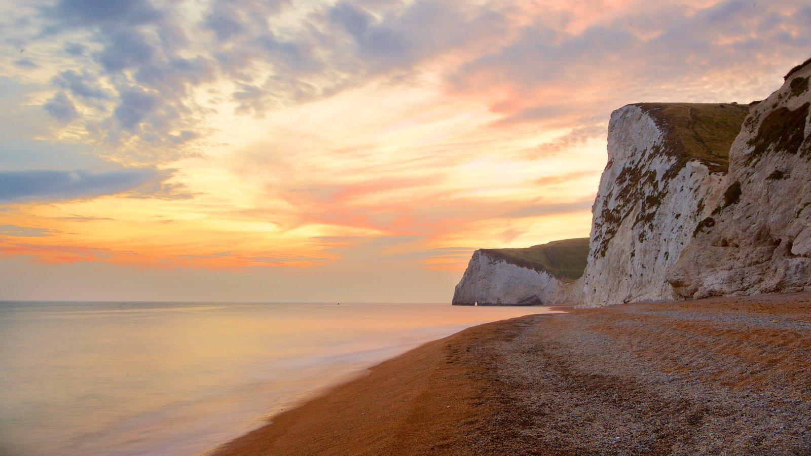 Durdle Door which includes a pebble beach, rugged coastline and a sunset