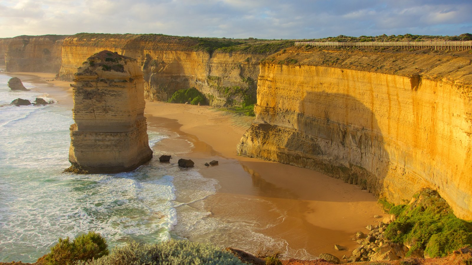 Twelve Apostles showing rugged coastline, a gorge or canyon and a sunset