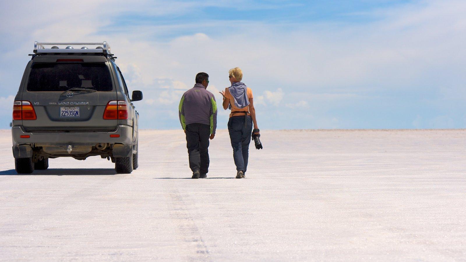 Salar de Uyuni caracterizando passeios e cenas tranquilas assim como um pequeno grupo de pessoas