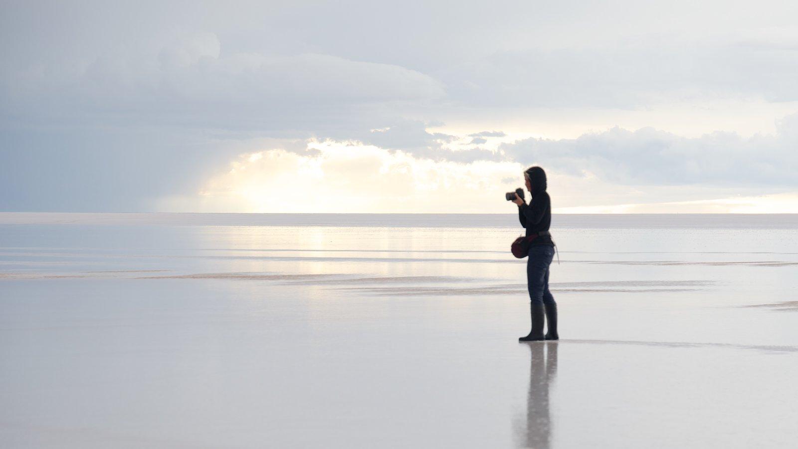 Salar de Uyuni que inclui paisagem e cenas tranquilas assim como uma mulher sozinha