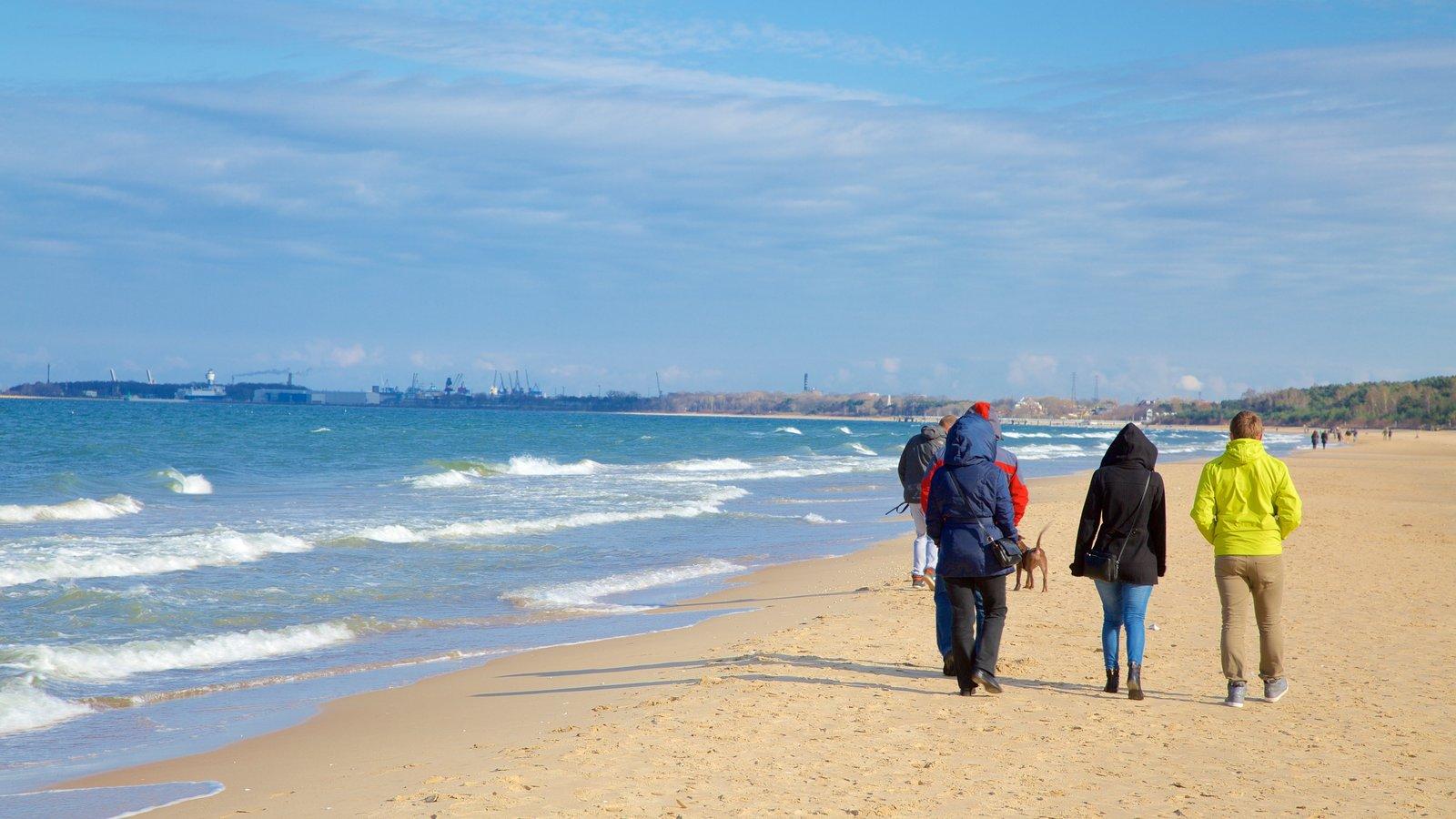 Praia Jelitkowo caracterizando uma praia assim como um pequeno grupo de pessoas
