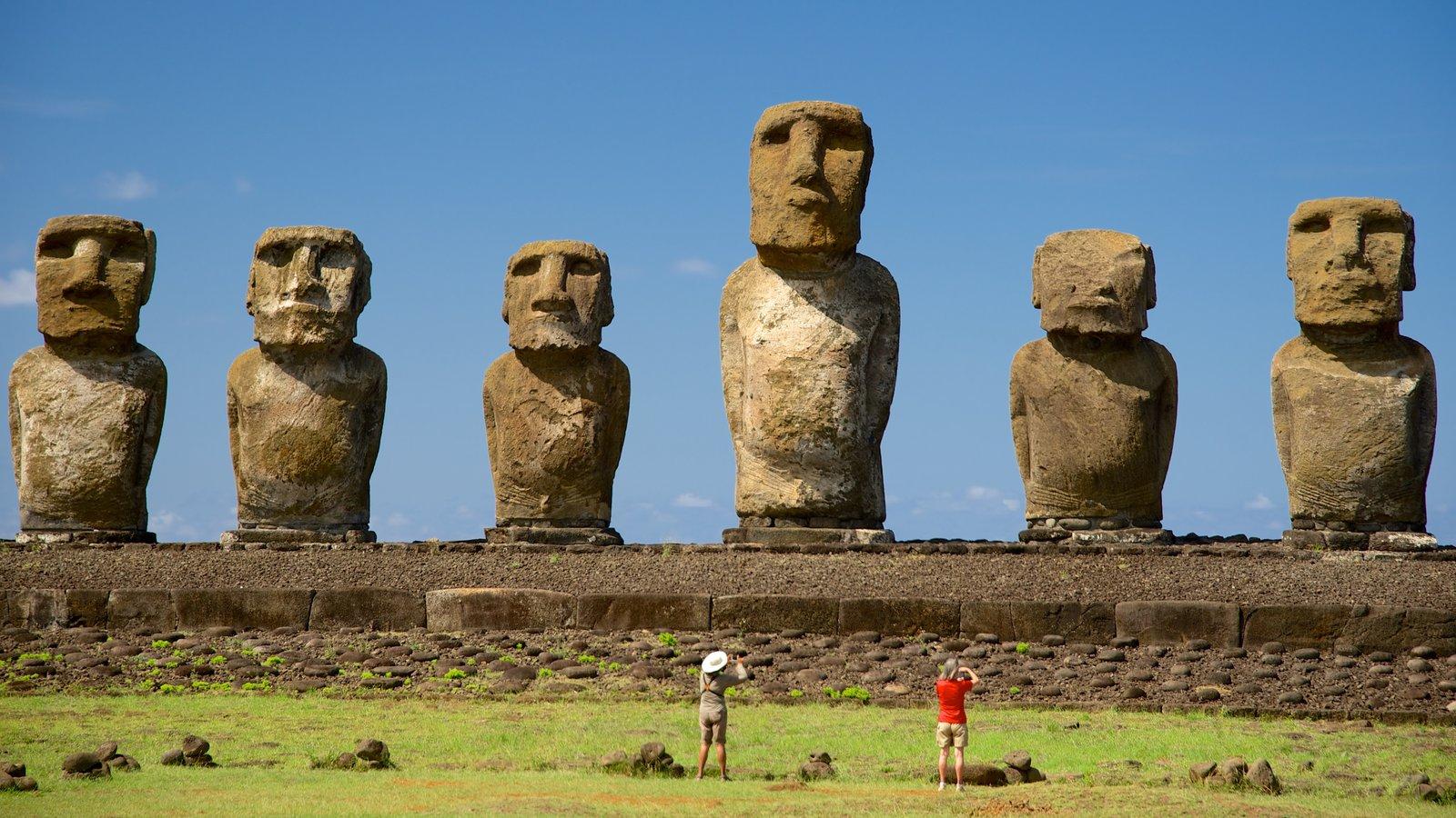 Ahu Tongariki mostrando elementos de patrimônio e uma estátua ou escultura assim como um pequeno grupo de pessoas