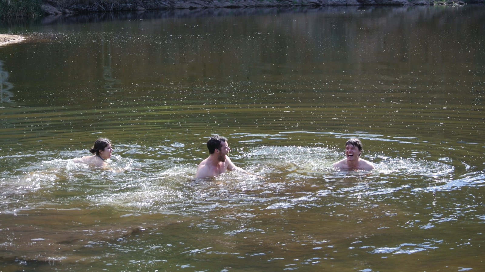 Uluru showing swimming and a river or creek as well as a small group of people