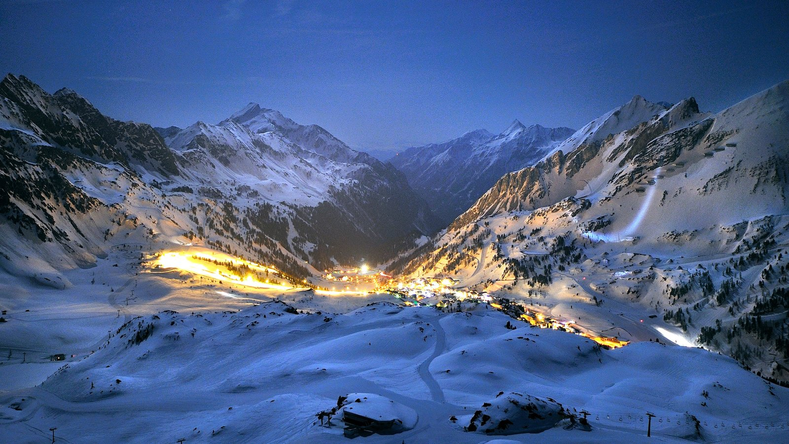 Obertauern which includes mountains, a small town or village and night scenes