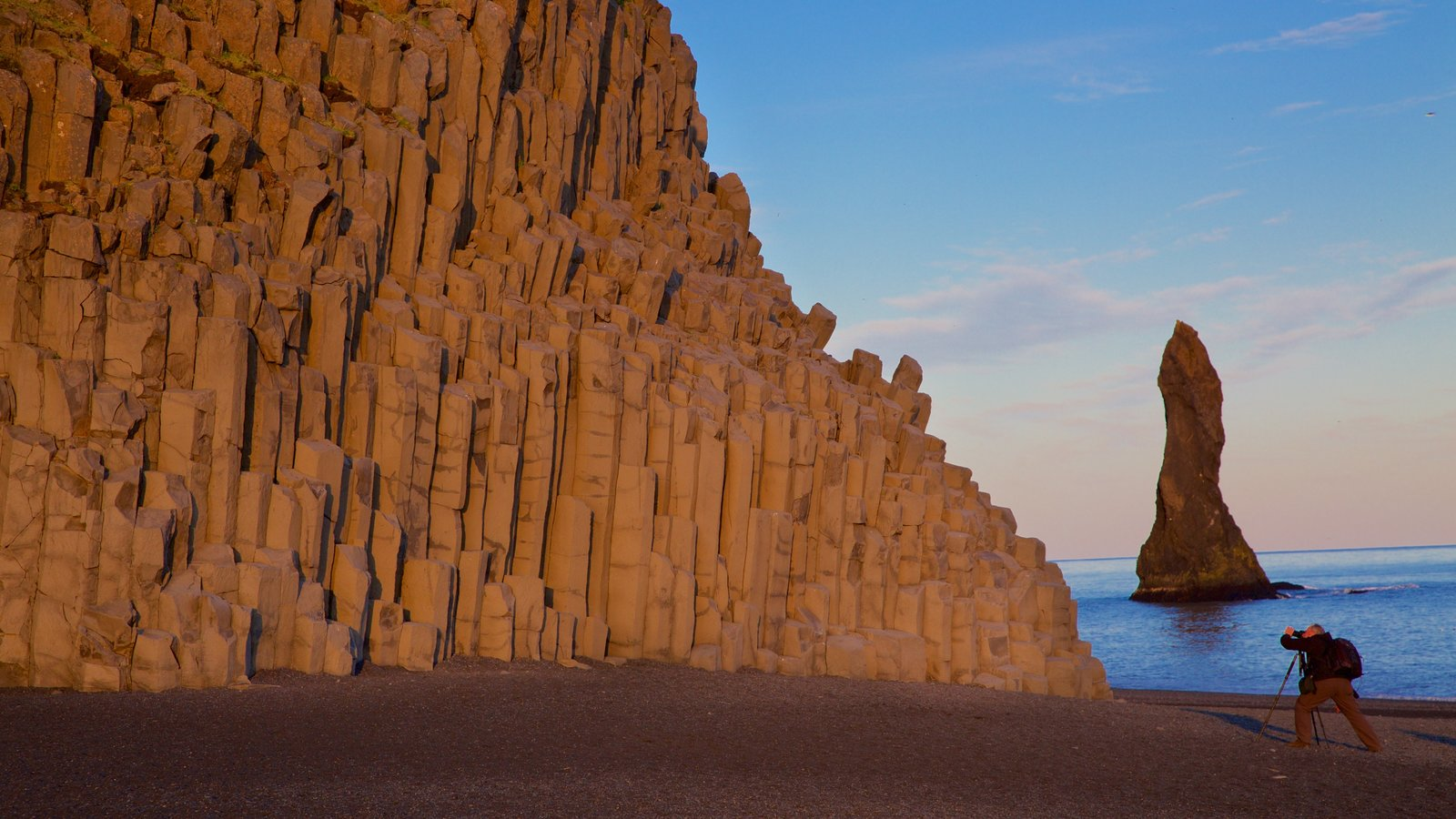 Reynisdrangar showing rocky coastline and a sunset as well as an individual male