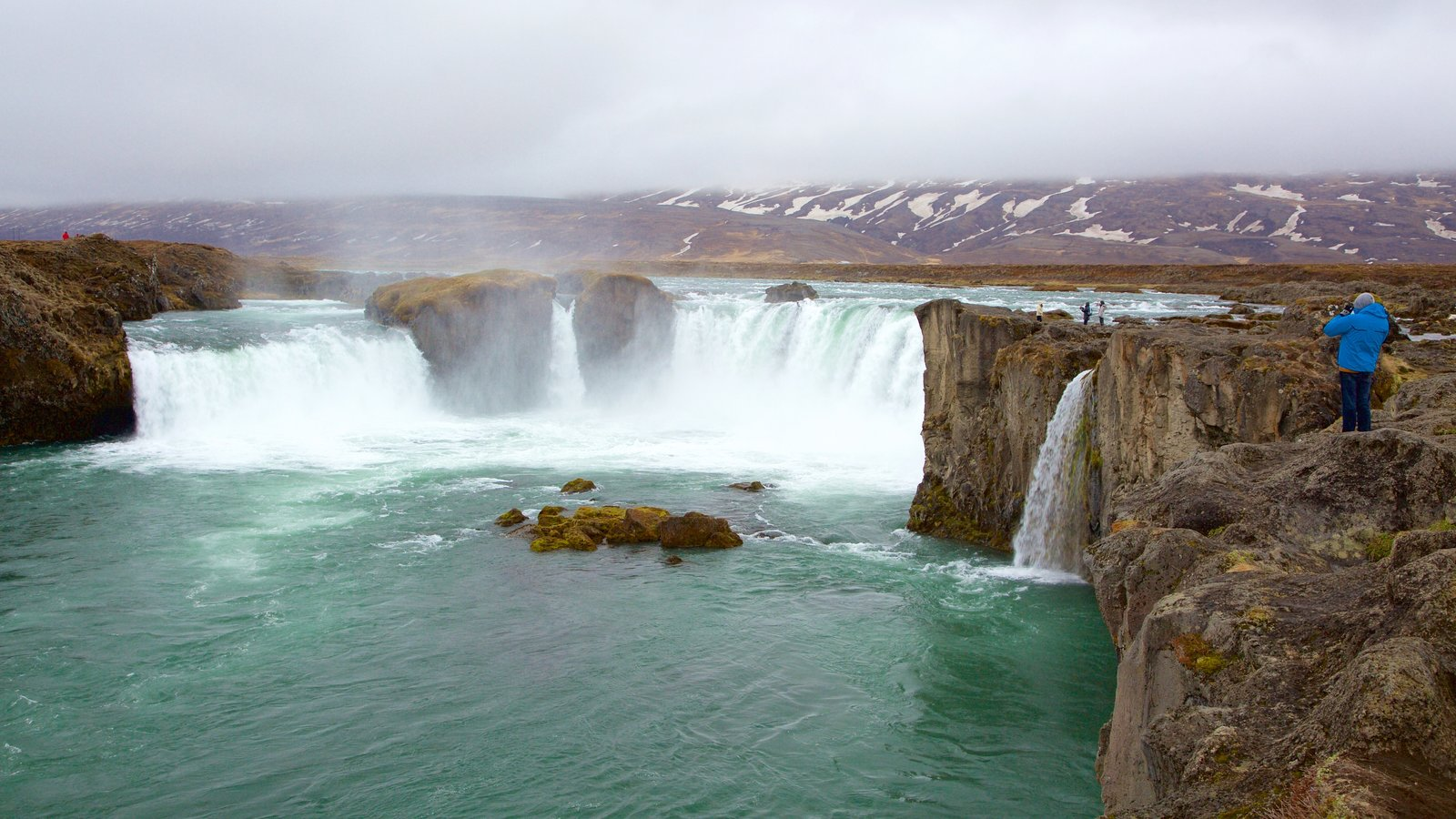 Godafoss showing a waterfall and mist or fog as well as an individual male