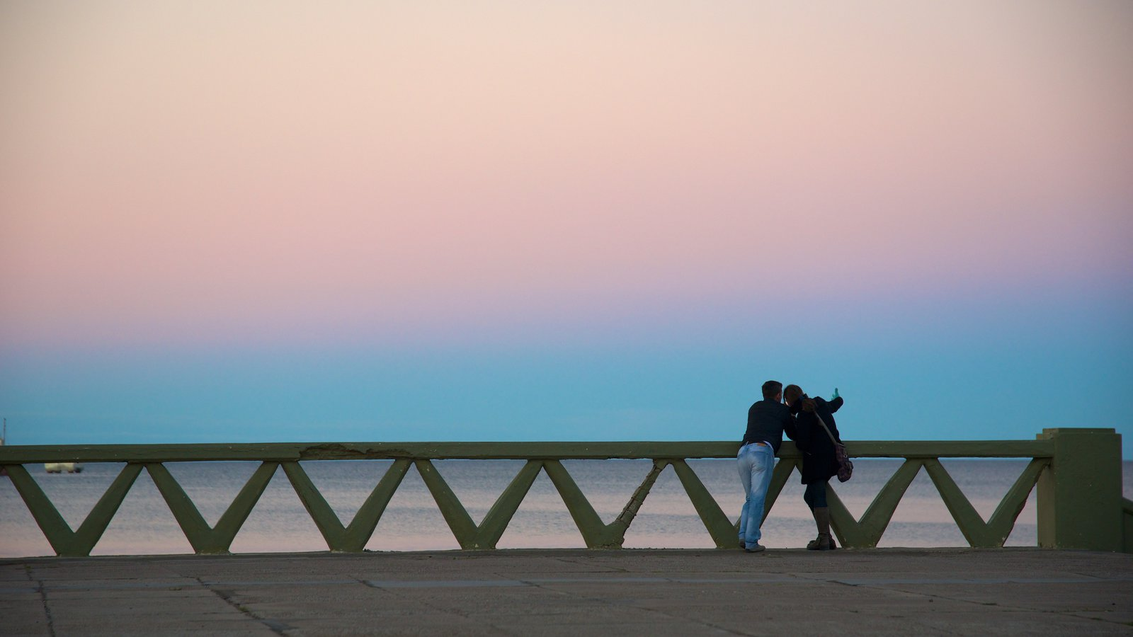 Puerto Madryn Beach featuring a sunset as well as a couple
