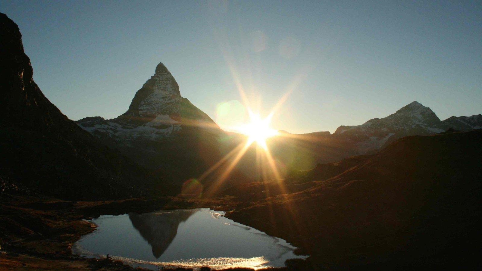 Matterhorn mostrando una puesta de sol, un lago o abrevadero y montañas