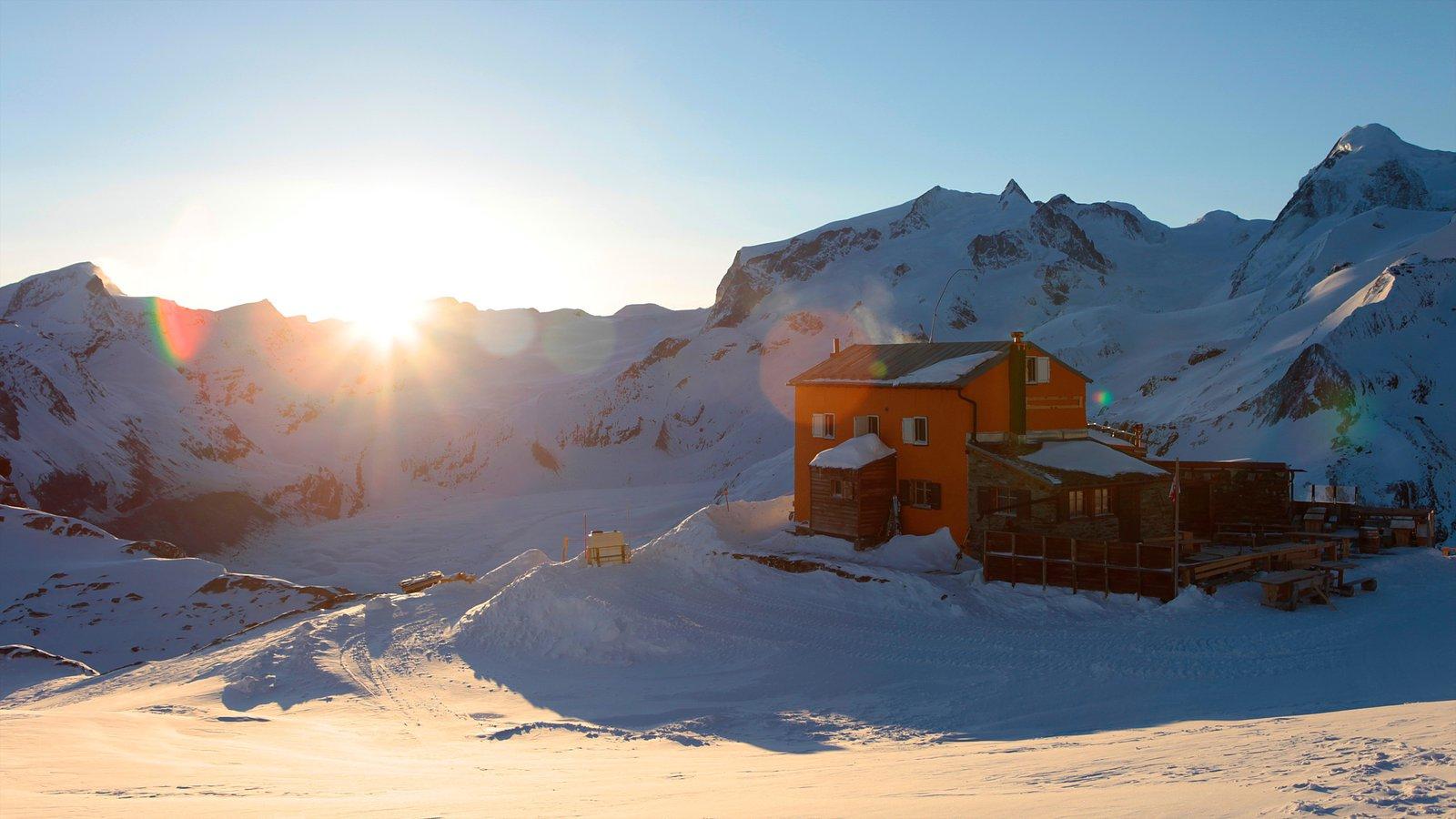 Matterhorn que incluye nieve, una puesta de sol y una casa