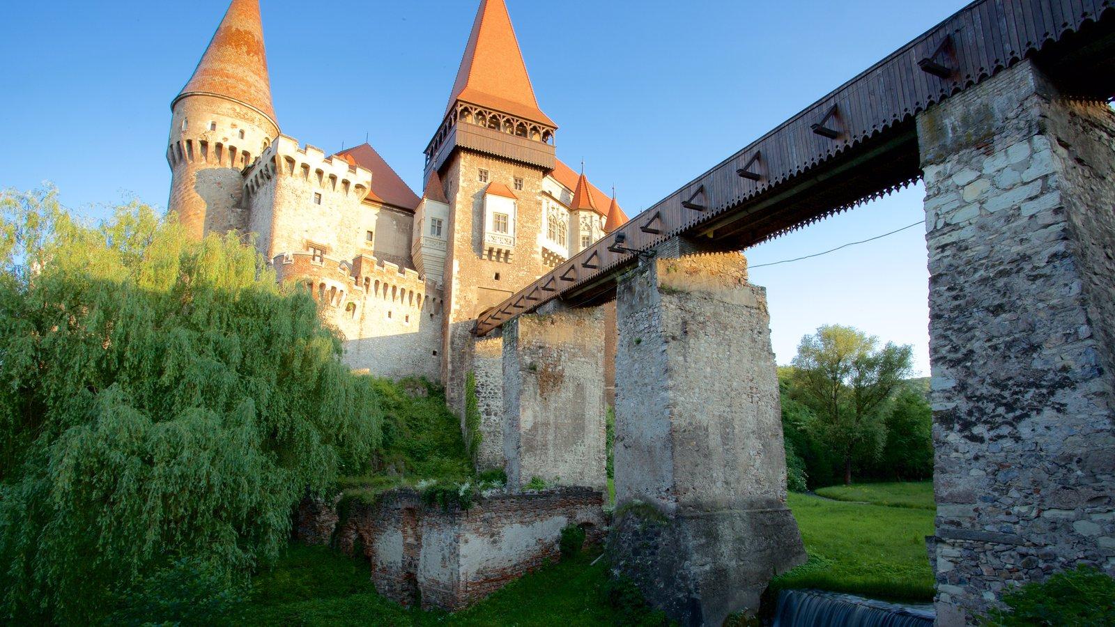 Castillo de Hunedoara mostrando un castillo, un puente y una puesta de sol