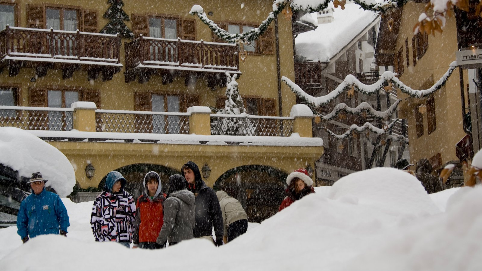 Courmayeur featuring snow as well as a small group of people