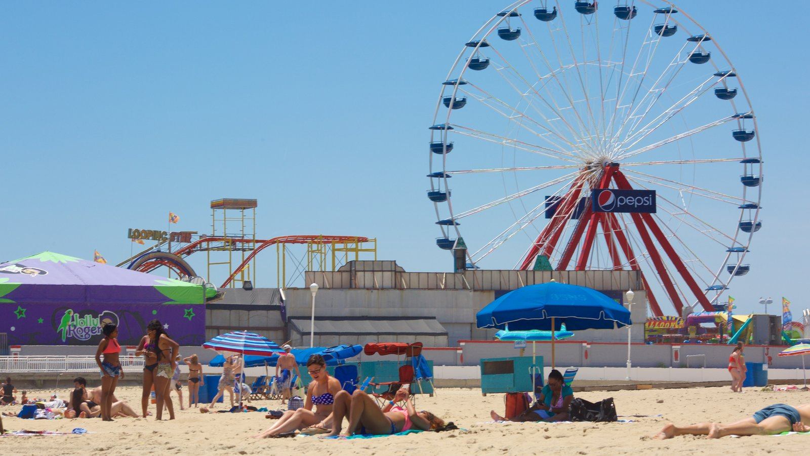 Ocean City Beach which includes rides and a sandy beach as well as a small group of people