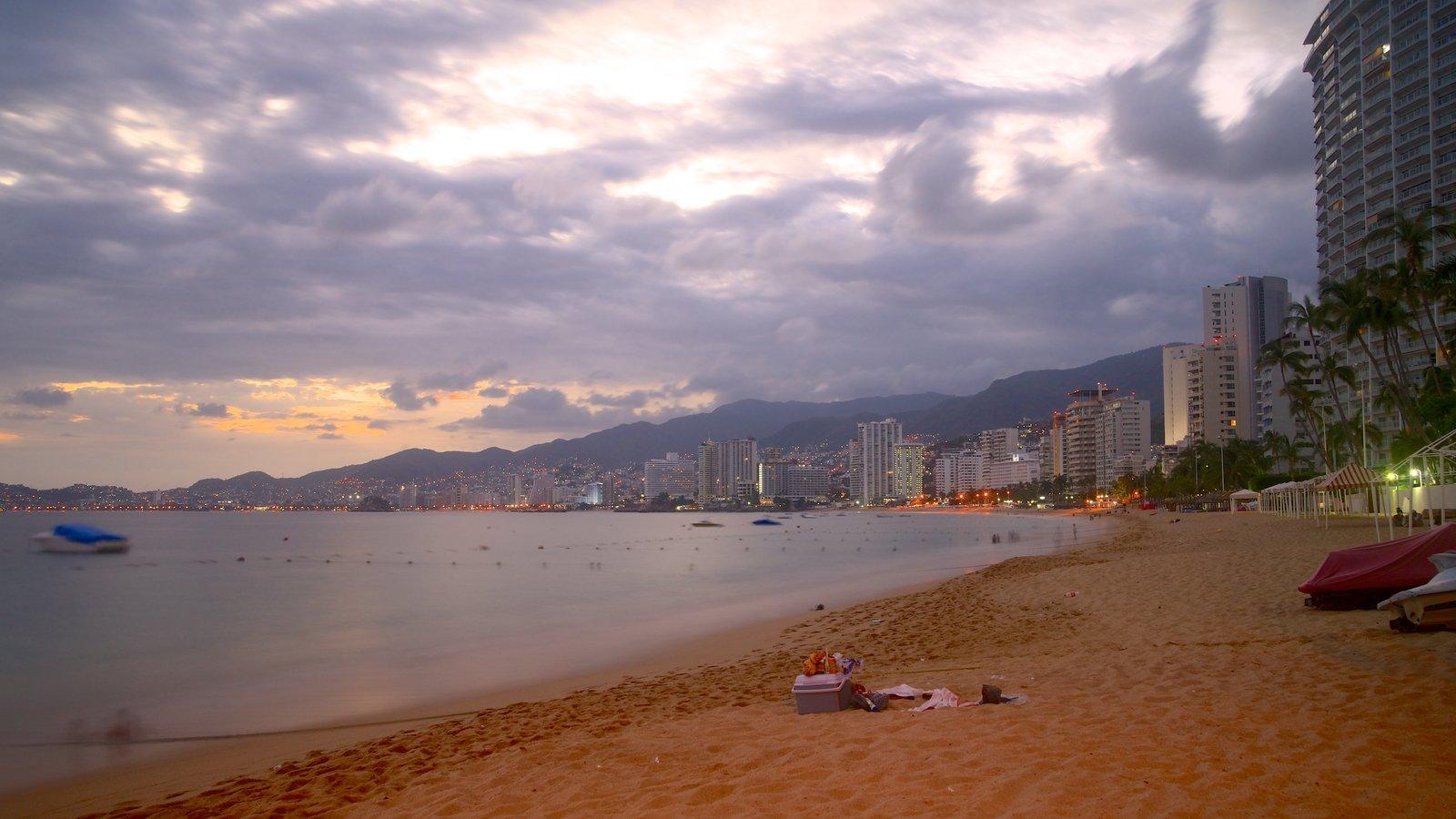 Playa Icacos mostrando una puesta de sol, una playa y una ciudad costera
