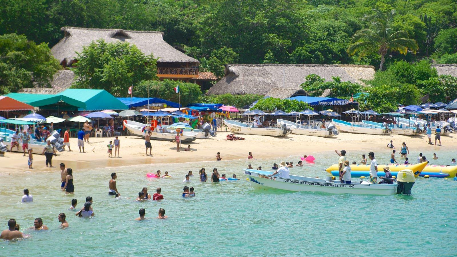 Playa Puerto Angelito que incluye paseos en lancha, una playa y una ciudad costera