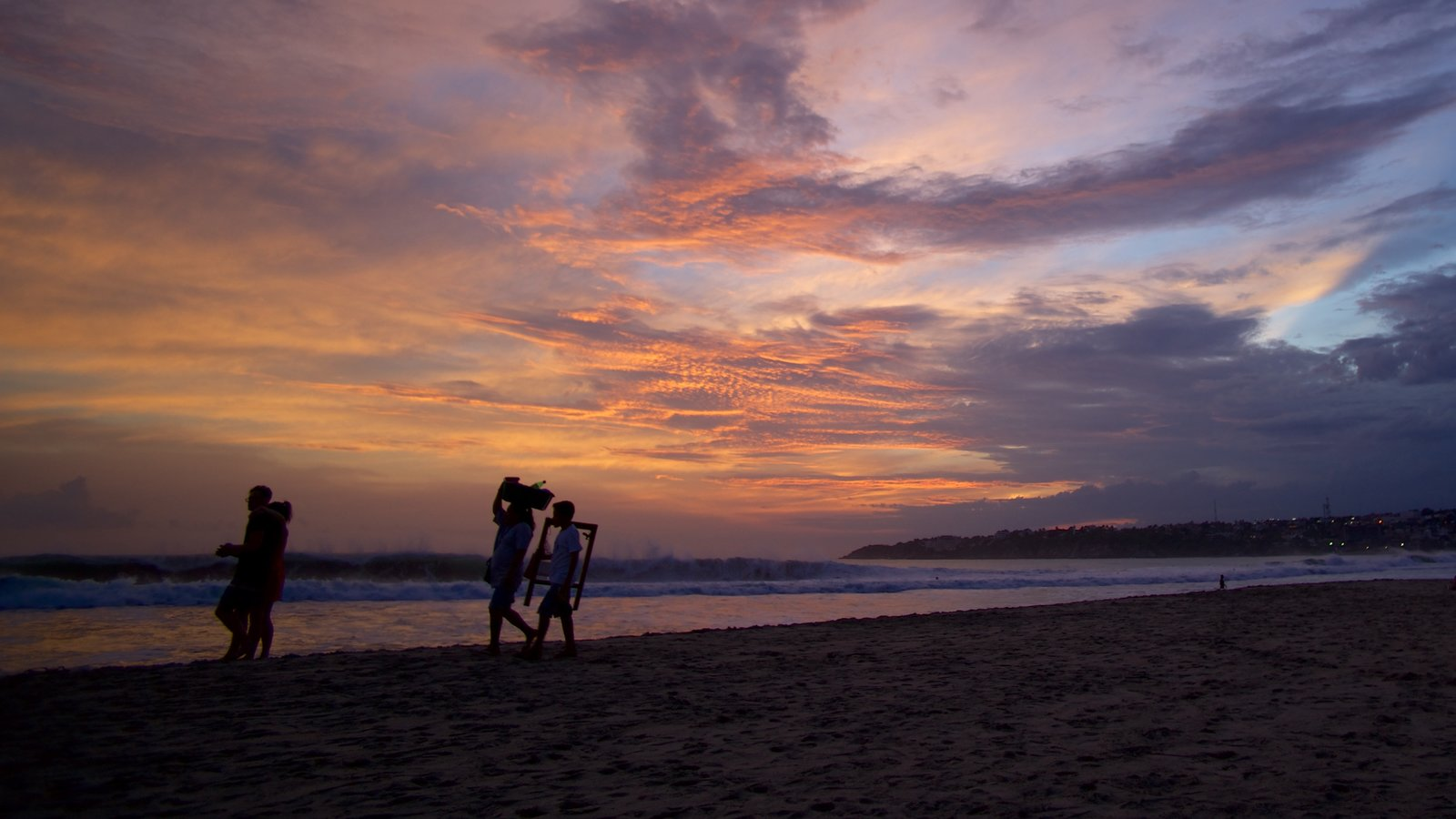 Puerto Escondido showing a sunset and a beach as well as a small group of people