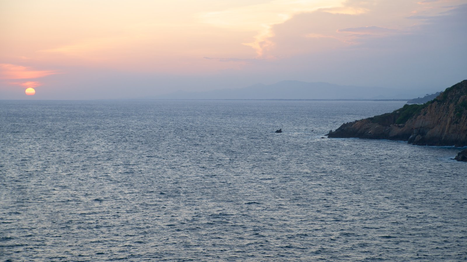 Sinfonía mostrando costa rocosa, vistas de paisajes y una puesta de sol