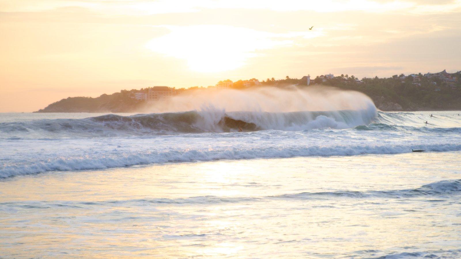 Playa Zicatela mostrando vistas generales de la costa, una puesta de sol y olas