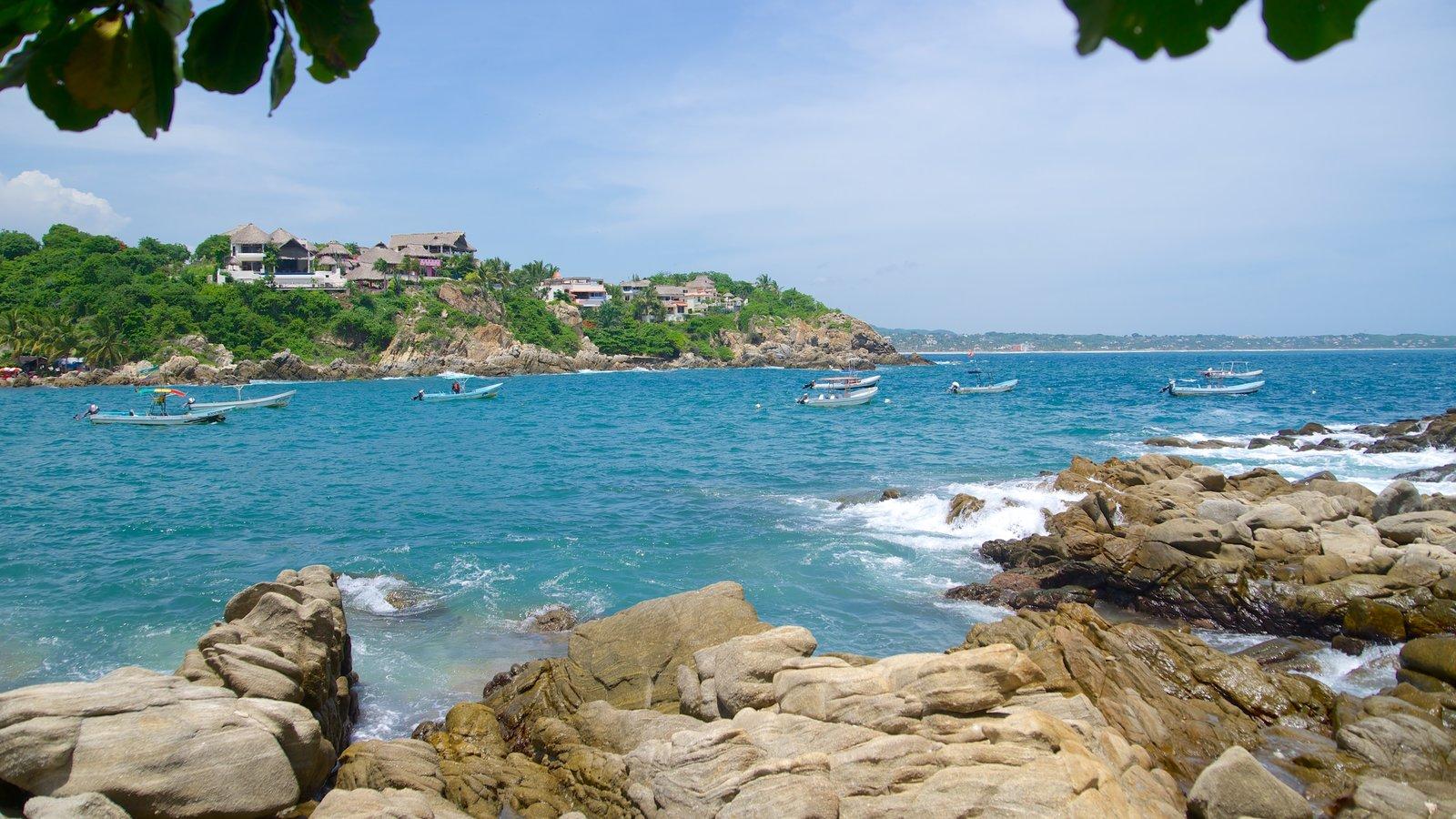 Playa Puerto Angelito que incluye una bahía o puerto y costa escarpada