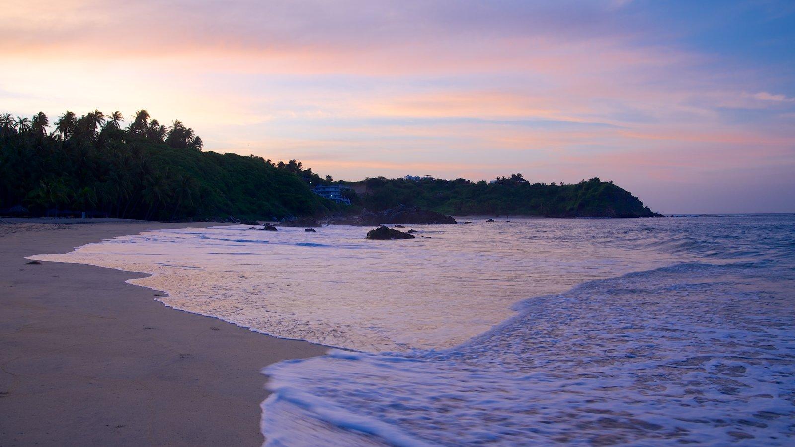Playa Bacocho mostrando una playa, costa rocosa y una puesta de sol