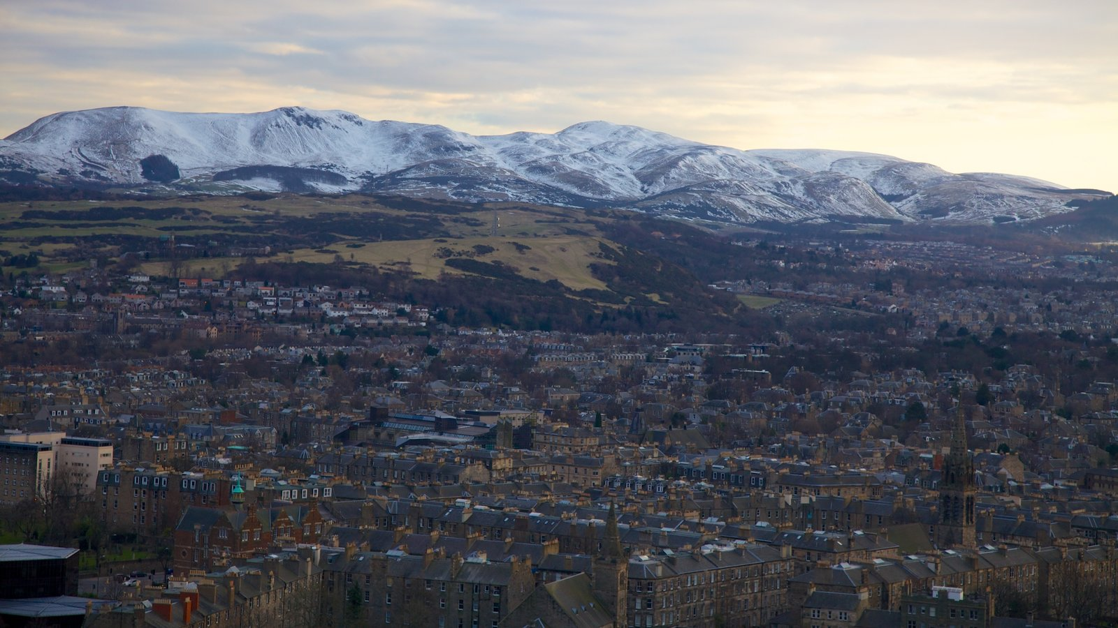 Arthur\\\'s Seat which includes mountains, a city and snow