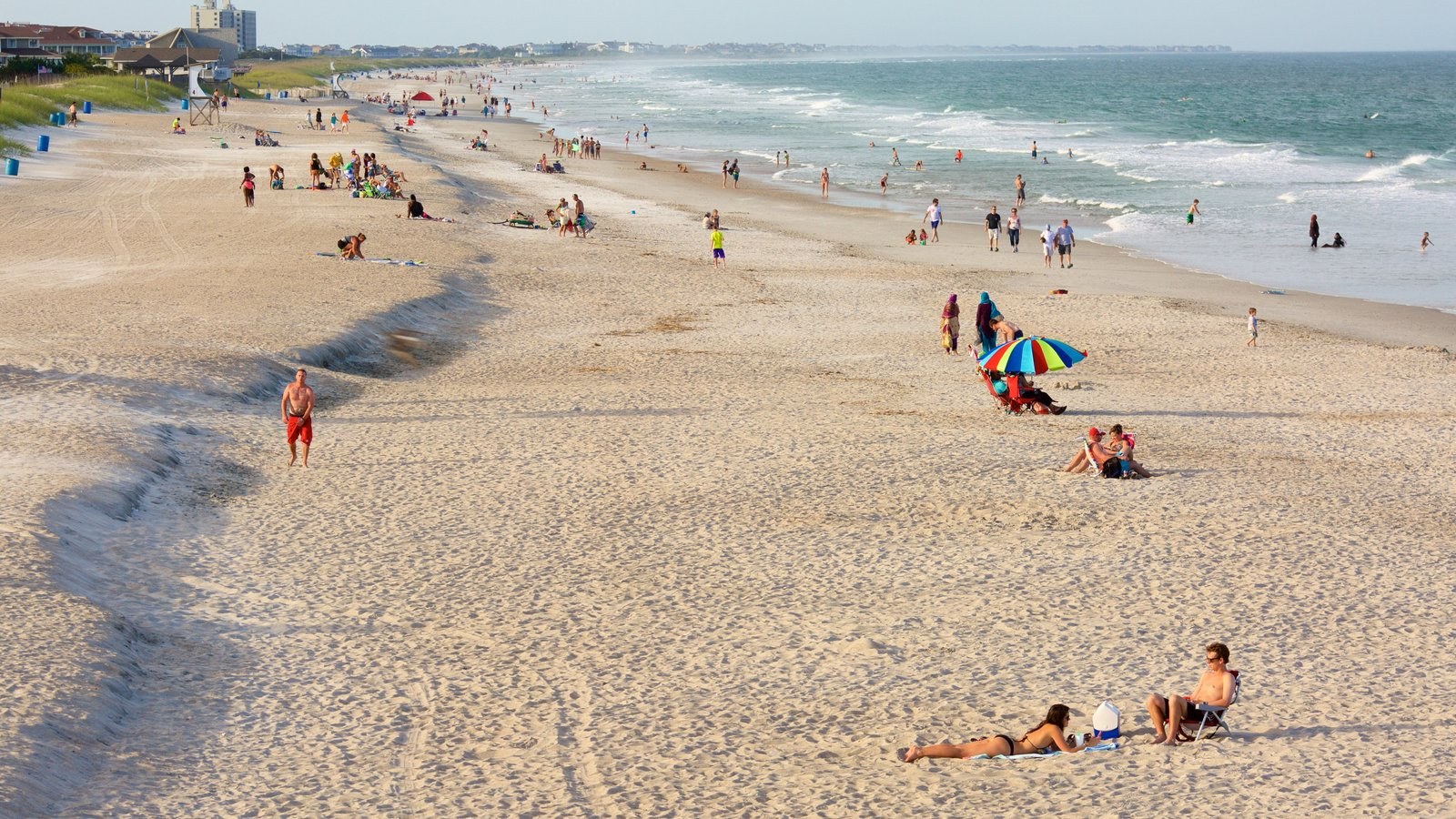 Wrightsville Beach which includes general coastal views and a sandy beach as well as a large group of people