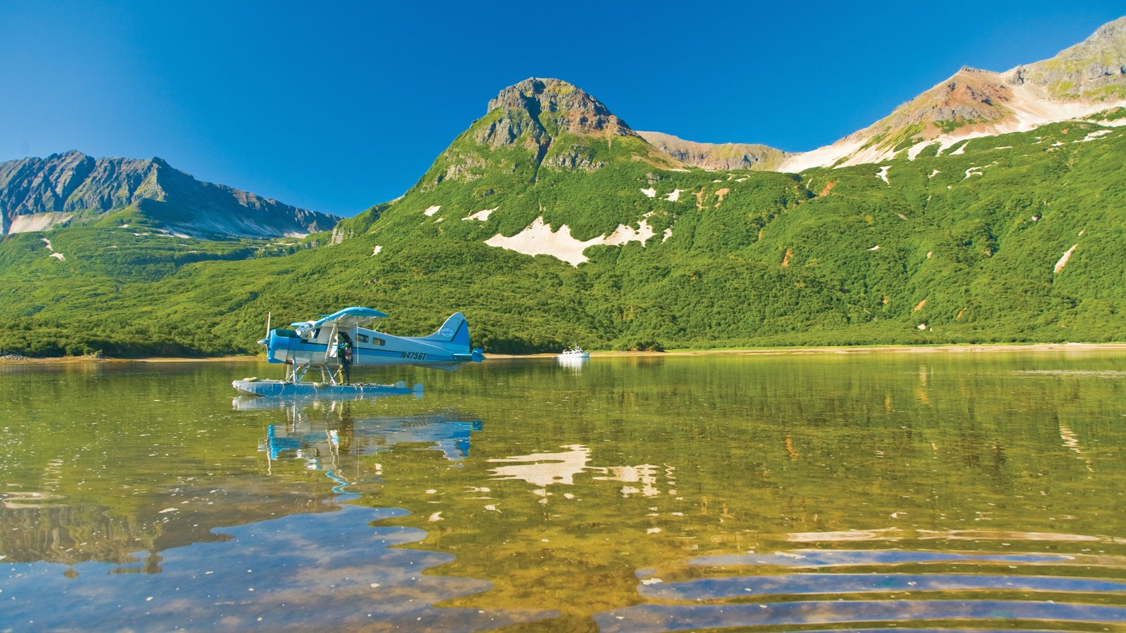 Southwest Alaska which includes a lake or waterhole, mountains and aircraft