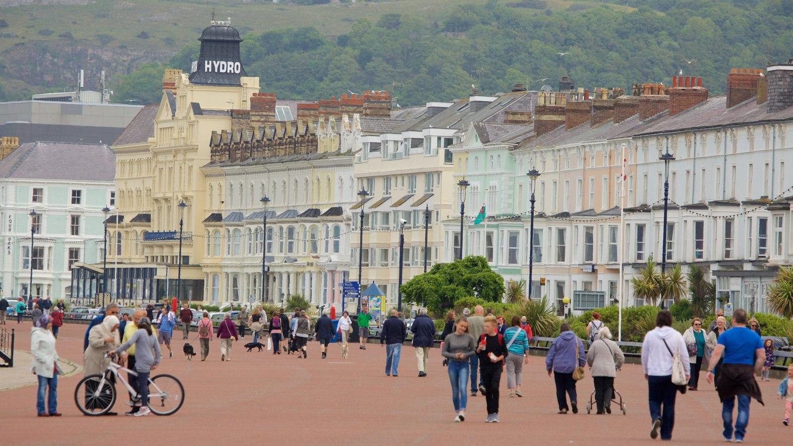 Llandudno que incluye una pequeña ciudad o pueblo y un parque o plaza y también un gran grupo de personas